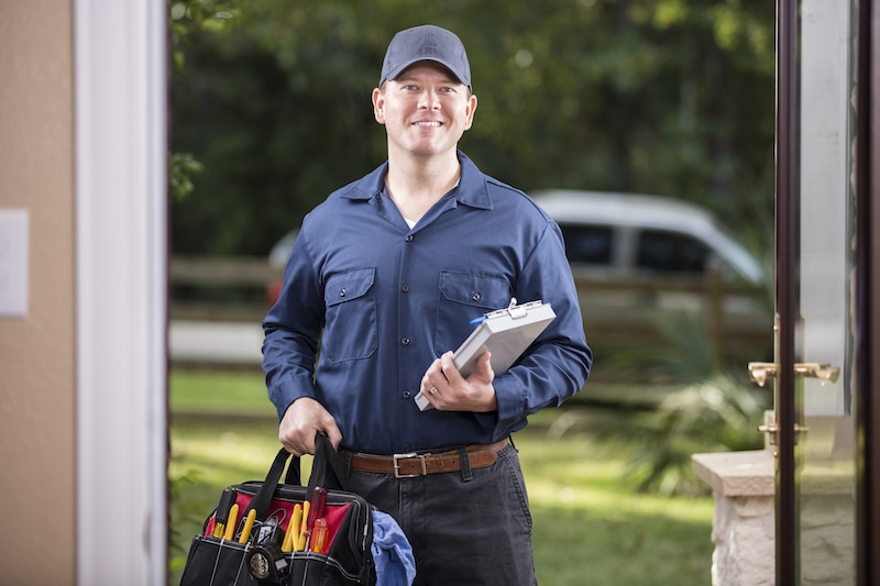 Caucasian repairman or blue collar/service industry worker makes service/house call at customer's front door. He holds his clipboard and tool box filled with work tools. Inspector, exterminator, electrician. He wears a navy blue uniform. Service truck seen in background parked on road.
