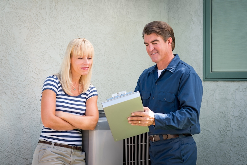 Air conditioner repairman in uniform and a clipboard discussing contract with housewife.